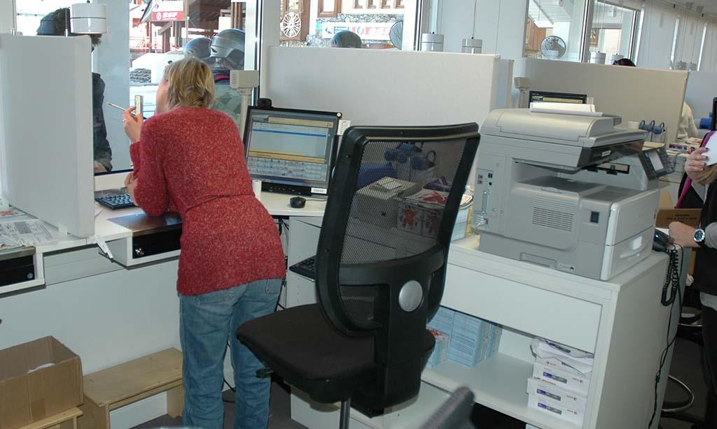 Personne travaillant au niveau d'un guichet ergonomique ou caisse vitrée